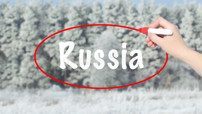 Mano de la mujer que escribe Rusia con un marcador sobre bosque del invierno imagenes de archivo