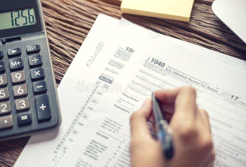 Mano de la mujer que escribe U S forma de impuesto 1040, usando declaraci?n sobre la renta individual de la calculadora, impuesto fotografía de archivo libre de regalías