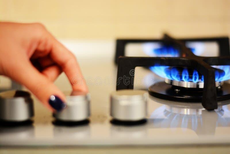 Mano de la mujer que gira la llama de la estufa imágenes de archivo libres de regalías