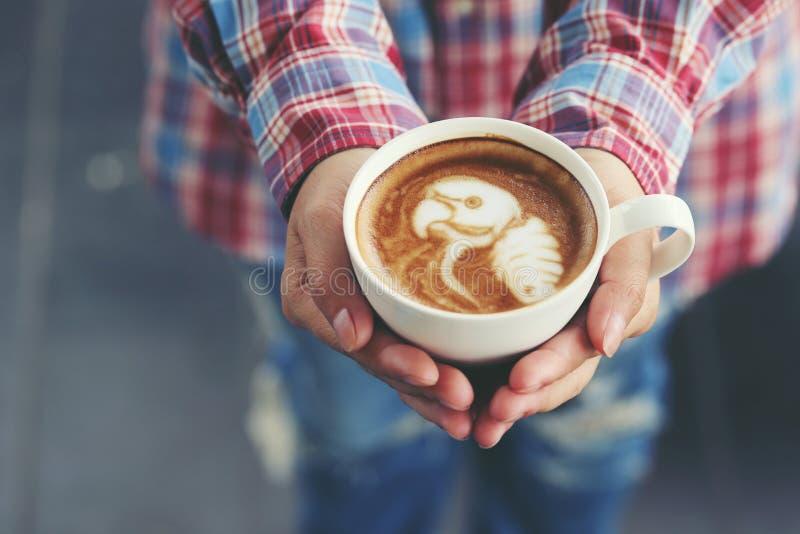 Mano de la mujer que lleva a cabo arte del latte del café con el modelo el loro en c foto de archivo libre de regalías