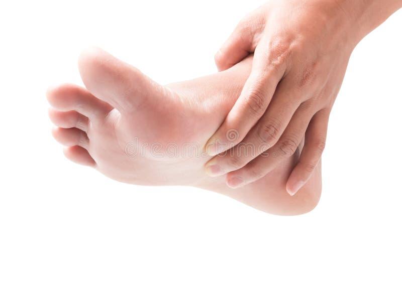 Mano de la mujer que lleva a cabo el pie con dolor, atención sanitaria y conce médico imagen de archivo libre de regalías