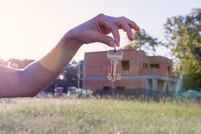 Mano de la mujer que lleva a cabo llaves de la casa imagenes de archivo