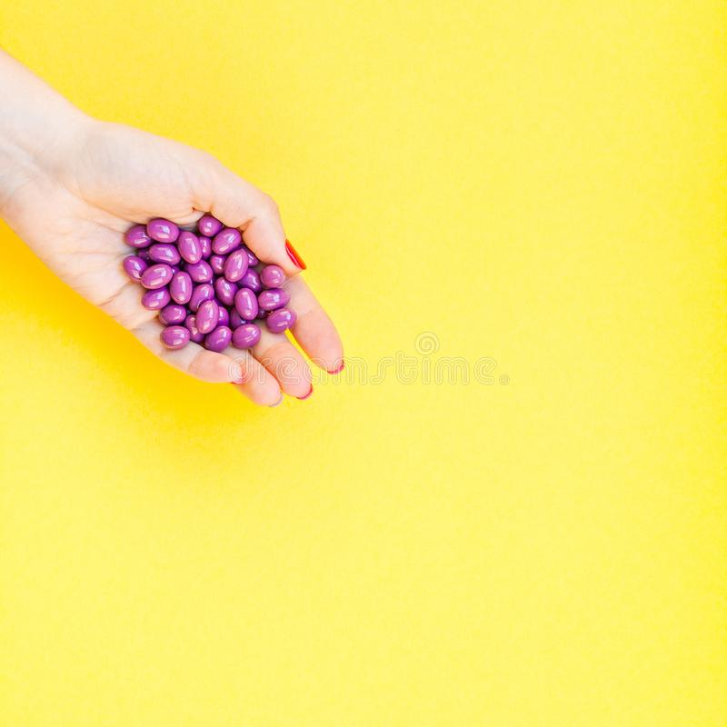 Mano de la mujer que lleva a cabo puñado púrpura de las píldoras fotos de archivo libres de regalías