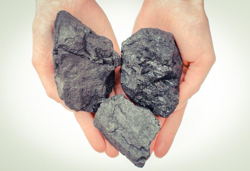 Mano de la mujer que lleva a cabo terrones, el combustible y el poder del carbón fotos de archivo