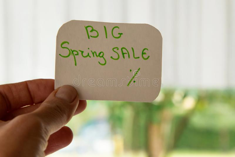 Mano de la mujer que lleva a cabo un mensaje de la tarjeta para la venta de la primavera fotos de archivo libres de regalías