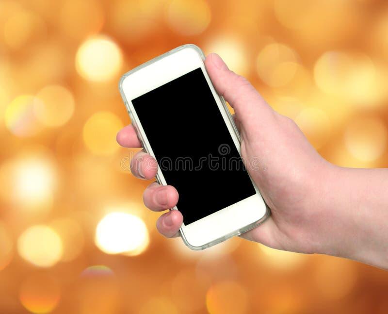 Mano de la mujer que muestra el teléfono elegante con la pantalla aislada en c borrosa fotografía de archivo libre de regalías