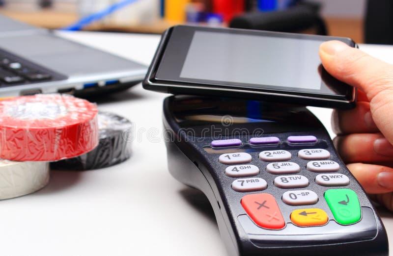 Mano de la mujer que paga con el lector de la tarjeta de crédito y el teléfono móvil con tecnología de NFC imagen de archivo libre de regalías