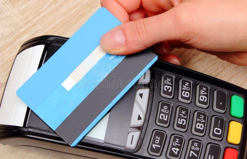 Mano de la mujer que paga con la tarjeta de crédito sin contacto con la tecnología de NFC, concepto de las finanzas imagen de archivo