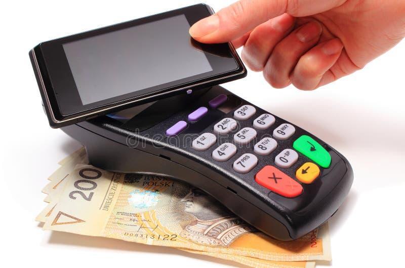 Mano de la mujer que paga con tecnología de NFC en el teléfono móvil fotografía de archivo