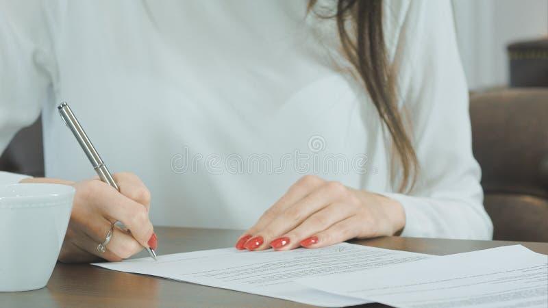 Mano de la mujer que pone la firma en contrato fotografía de archivo