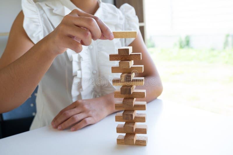 Mano de la mujer que pone la madera del bloque cuidadosamente, la gestión de riesgos del concepto y el plan de la estrategia fotos de archivo