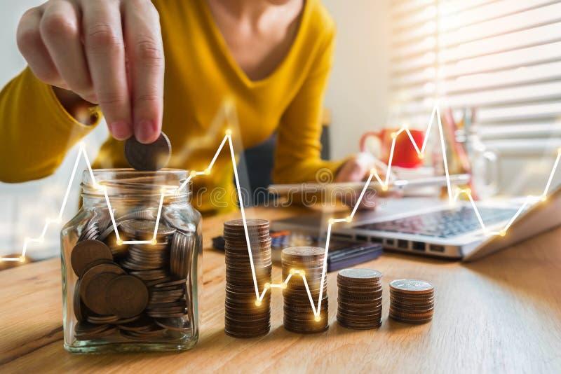 Mano de la mujer que pone monedas en el vidrio para el dinero de ahorro fotos de archivo