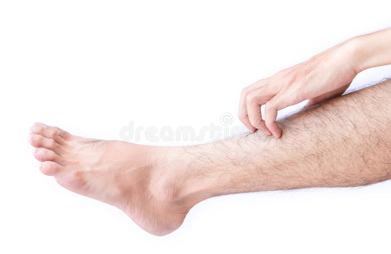 Mano de la mujer que rasguña en pies con el fondo blanco para sano imagen de archivo