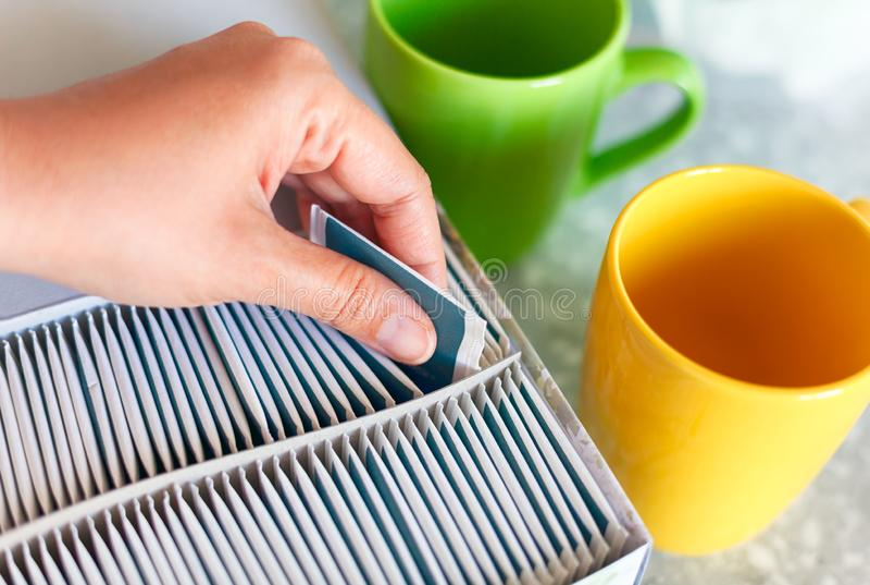 Mano de la mujer que saca la bolsita de té de la caja con dos tazas en la tabla de cocina foto de archivo libre de regalías
