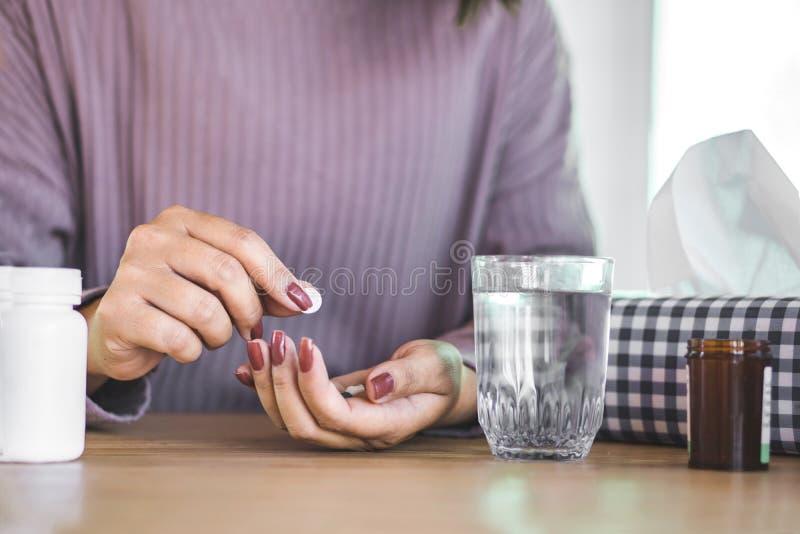 Mano de la mujer que se prepara para tomar la medicina con el vaso de agua y la botella de píldora en el escritorio foto de archivo