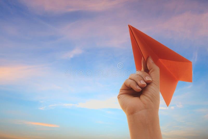 Mano de la mujer que sostiene el cohete de papel rojo con el fondo del cielo azul Concepto de la libertad imagen de archivo