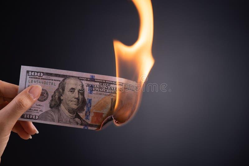 Mano de la mujer que sostiene el dinero ardiente ardiendo del efectivo del dólar sobre el fondo negro - finanzas del negocio, aho foto de archivo