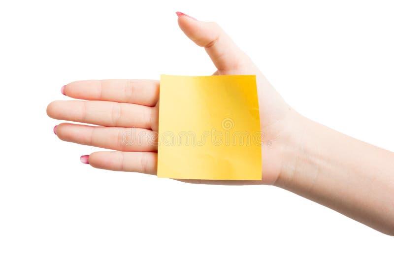 Mano de la mujer que sostiene el papel de carta amarillo en blanco imágenes de archivo libres de regalías