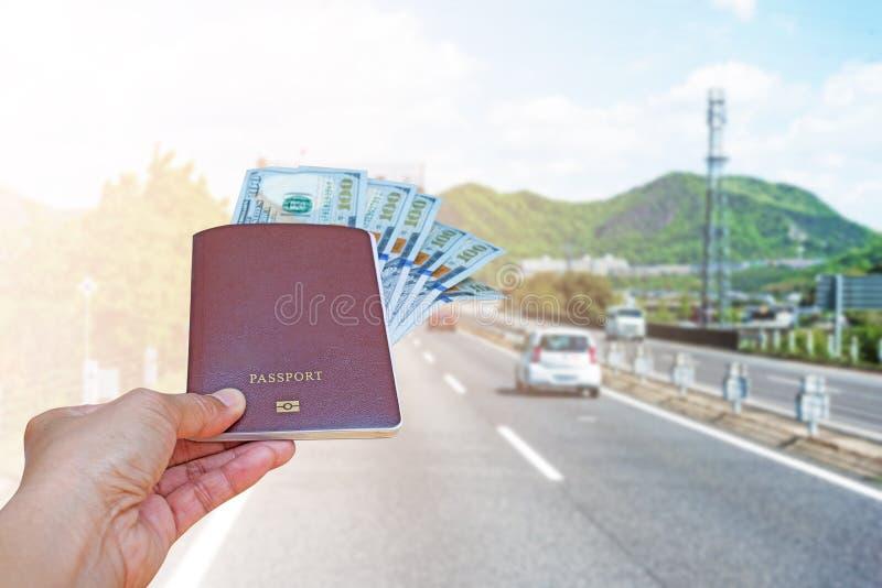 mano de la mujer que sostiene el pasaporte y el aislante americano de la moneda del dólar imagen de archivo