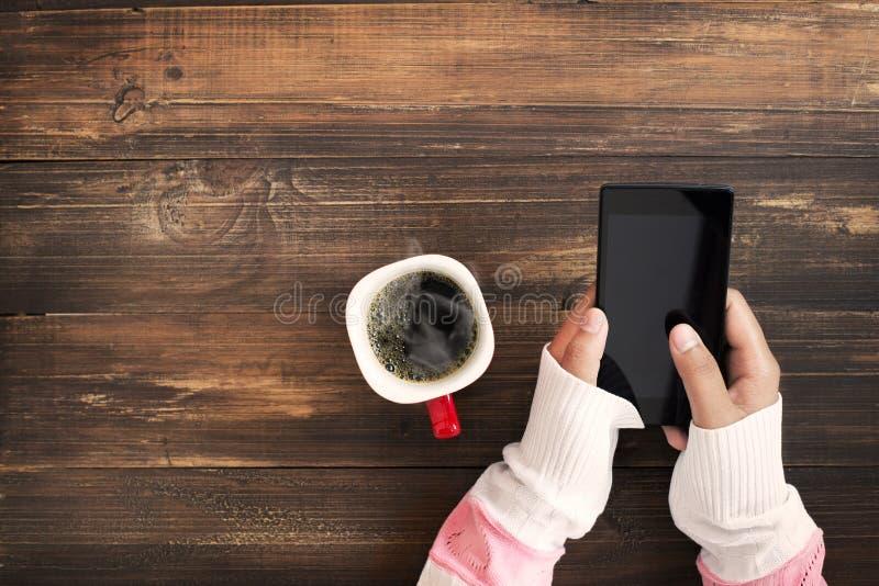Mano de la mujer que sostiene el teléfono elegante con la taza de café caliente en la tabla de madera foto de archivo