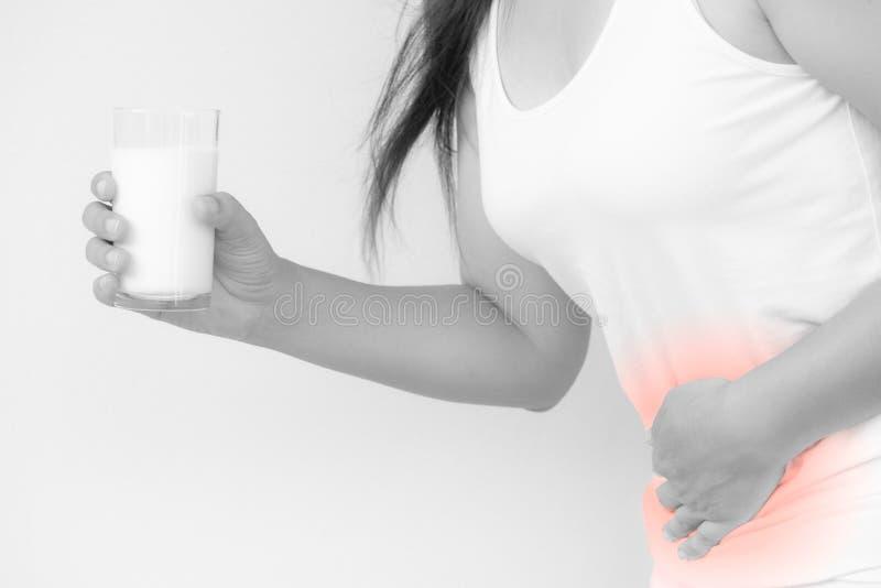 Mano de la mujer que sostiene el vidrio de leche que tiene mún dolor de estómago imágenes de archivo libres de regalías