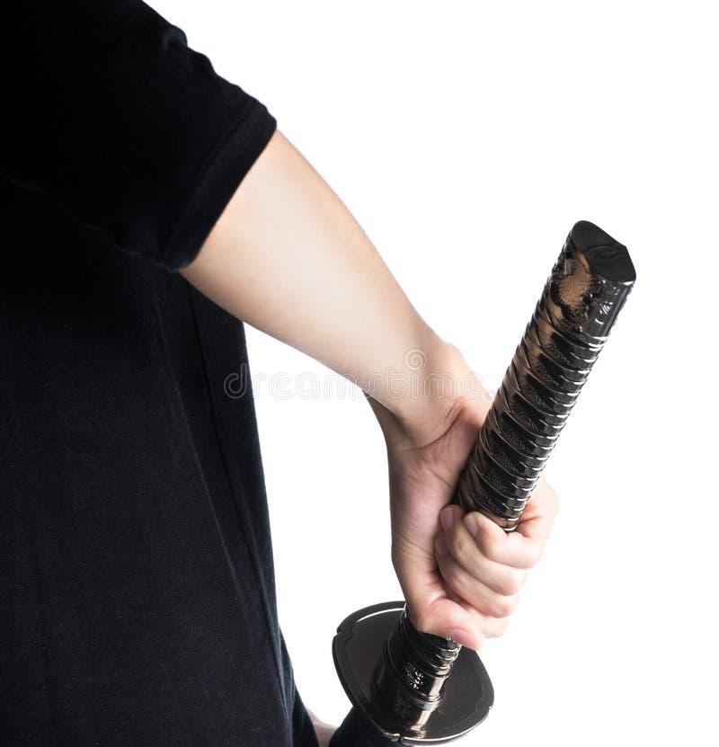 Mano de la mujer que sostiene la espada del samurai en el fondo blanco, aislado imagen de archivo