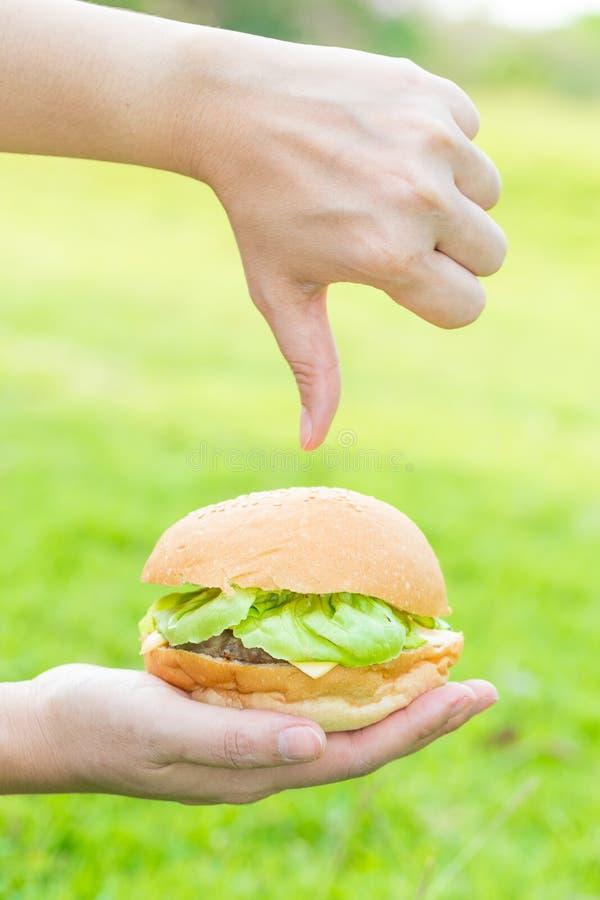 Mano de la mujer que sostiene la hamburguesa y los alimentos de preparación rápida de la aversión imagenes de archivo