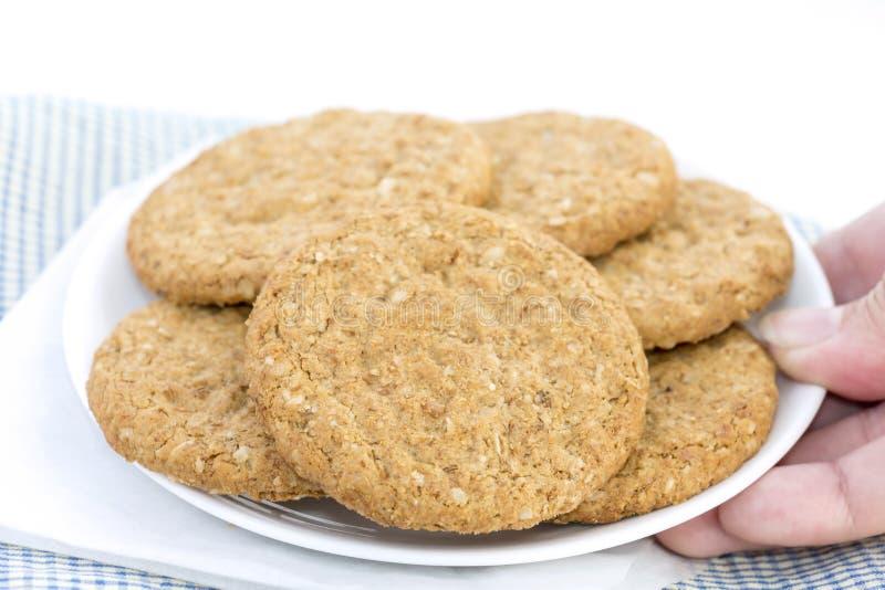 Mano de la mujer que sostiene las galletas de torta dulce hechas en casa hechas de pila de la harina de avena en placa en fondo a imagenes de archivo