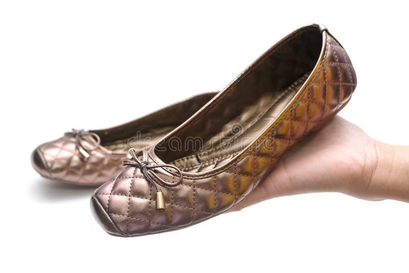 Mano de la mujer que sostiene los nuevos zapatos aislados foto de archivo libre de regalías