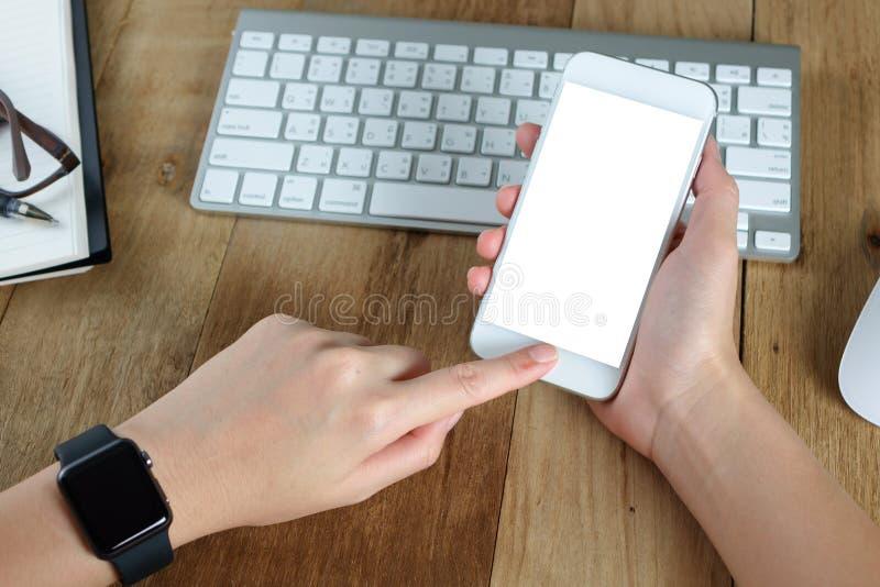 Mano de la mujer que sostiene la pantalla vacía del Smart-teléfono en el trabajo de escritorio de madera fotos de archivo libres de regalías