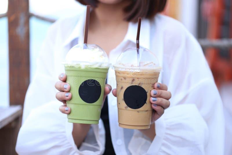 Mano de la mujer que sostiene té de verde helado del matcha y el café frío para la bebida del verano imagen de archivo libre de regalías