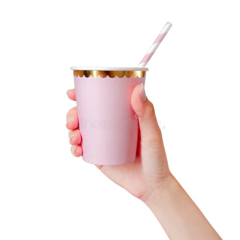 Mano de la mujer que sostiene la taza de papel rosada con la paja aislada en el fondo blanco Plantilla de la taza en blanco para  foto de archivo