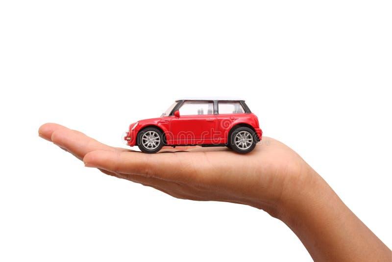Mano de la mujer que sostiene un coche rojo del juguete foto de archivo
