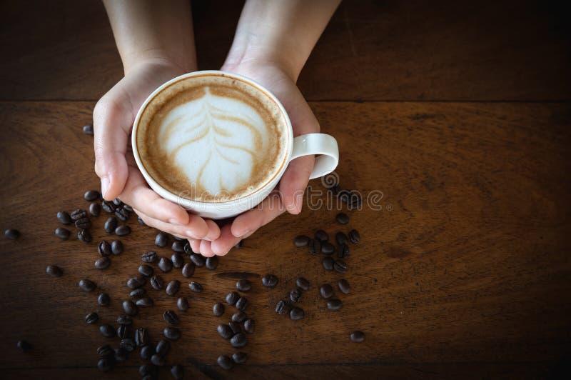 Mano de la mujer que sostiene una taza de caf? en una tabla de madera vieja, visi?n superior foto de archivo