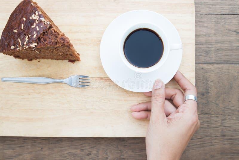 Mano de la mujer que sostiene una taza de café con una torta, forma de vida imágenes de archivo libres de regalías