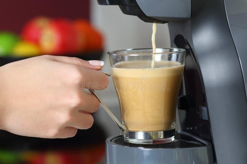 Mano de la mujer que sostiene una taza en un fabricante de café fotografía de archivo