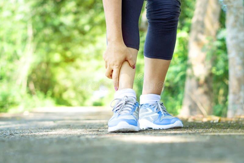 Mano de la mujer que toca su dolor de pierna debido al tobillo torcido quebrado de deporte fotografía de archivo libre de regalías