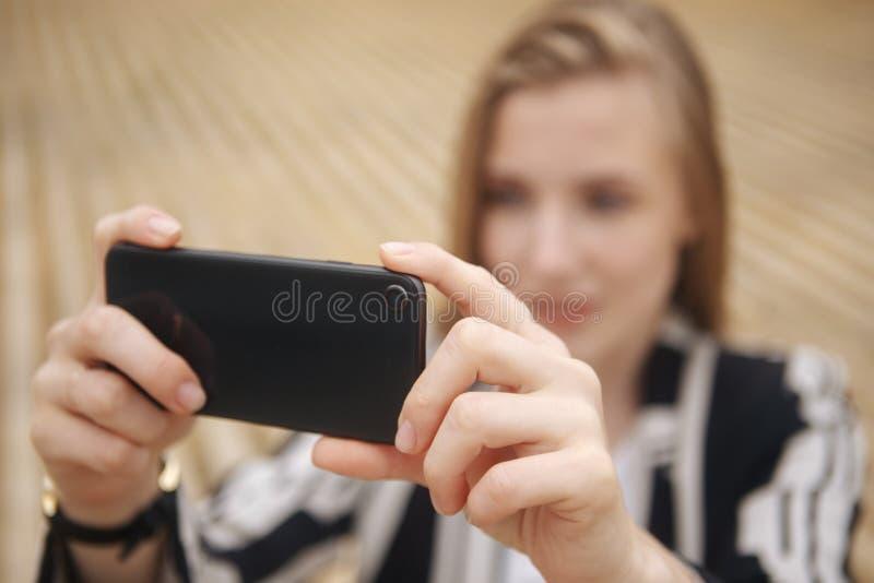 Mano de la mujer que toma la foto de la ciudad con un smartphone Ciérrese para arriba de las manos del ` s de la mujer Botones de foto de archivo