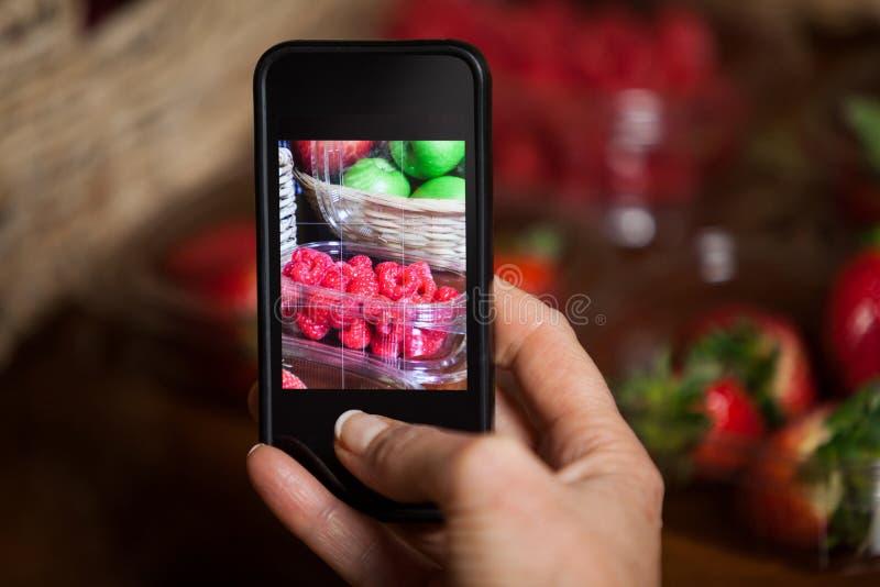 Mano de la mujer que toma la foto de frutas fotografía de archivo libre de regalías