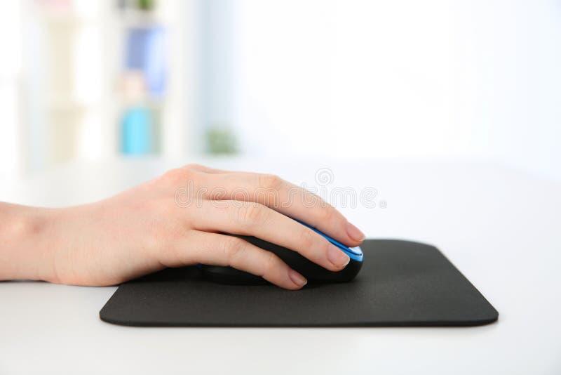 Mano de la mujer que trabaja con el ratón del ordenador fotos de archivo libres de regalías