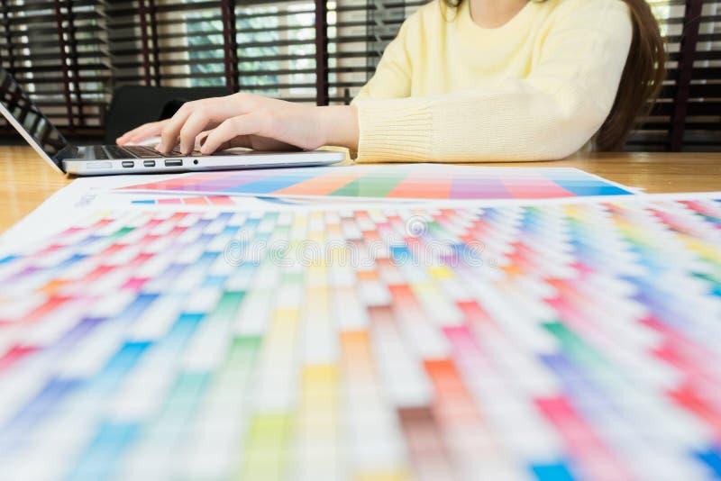 Mano de la mujer que trabaja con el teléfono y el ordenador portátil en el escritorio de madera en oficina puede ser utilizado en imágenes de archivo libres de regalías