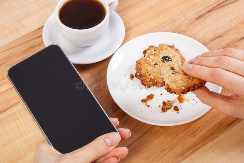 Mano de la mujer que usa el teléfono o el smartphone móvil, las galletas de harina de avena y la taza de café imagen de archivo