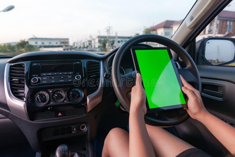 Mano de la mujer que usa la tableta con el monitor verde en blanco de la pantalla en el coche de SUV foto de archivo libre de regalías