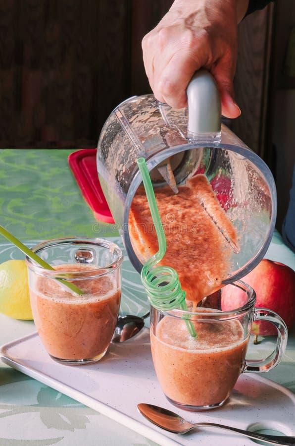 Mano de la mujer que vierte el smoothie de las frutas frescas imágenes de archivo libres de regalías