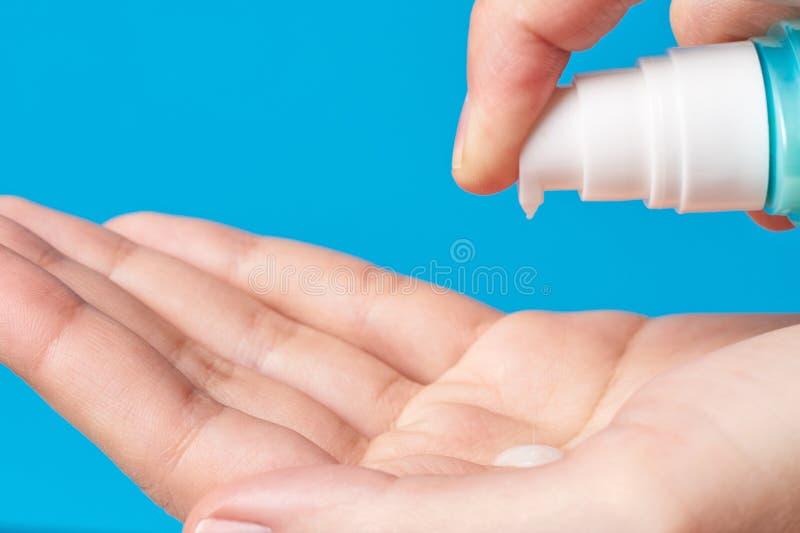 Mano de la mujer usando el dispensador en un fondo azul, cuidado de la bomba del gel de la higiene de la mano del lavado de piel  foto de archivo