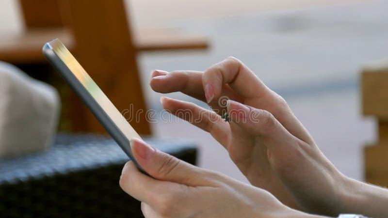 Mano de la mujer usando el dispositivo tecnológico de la tableta al aire libre imagen de archivo libre de regalías