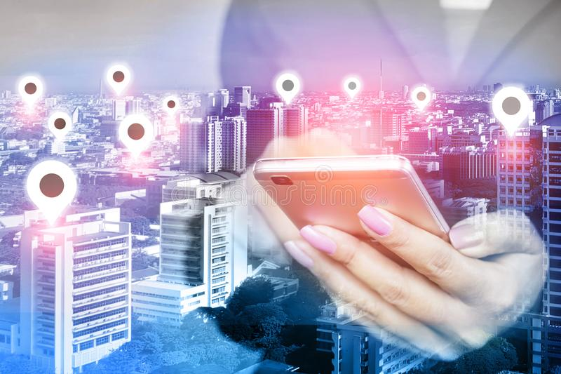 Mano de la mujer usando el teléfono móvil con el icono sobre ciudad elegante, concepto de la ubicación de la conexión de red foto de archivo
