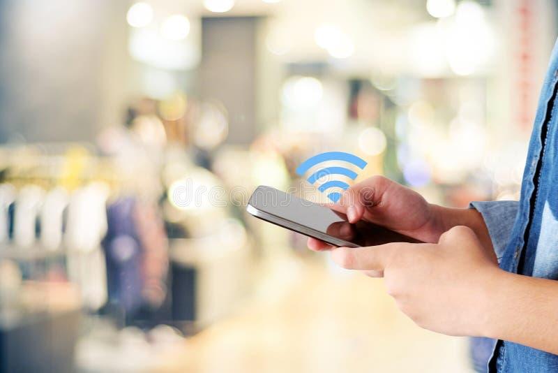 Mano de la mujer usando icono elegante del teléfono y del wifi sobre tienda de la falta de definición con imagenes de archivo