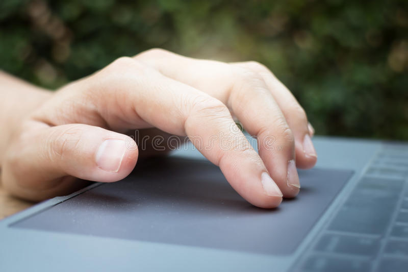 Mano de la mujer usando panel táctil del ordenador portátil fotos de archivo