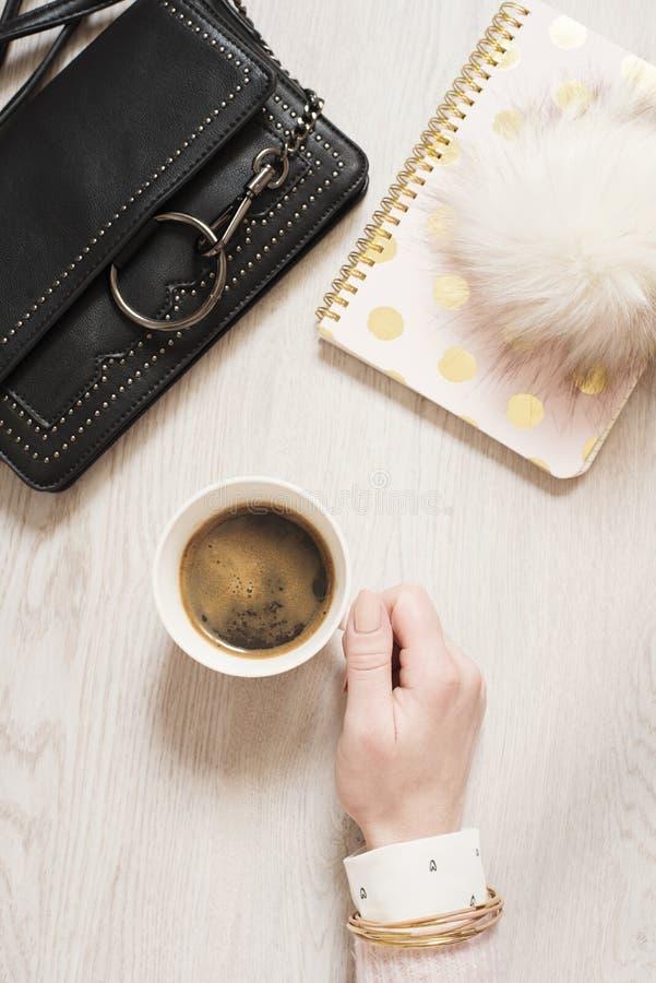 Mano de la mujer de la visión superior que sostiene la taza de café sólo en endecha del plano Espacio de trabajo con el cuaderno  fotos de archivo